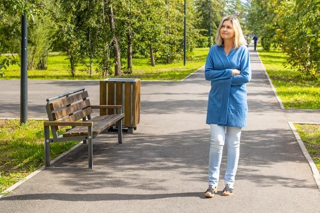Kobieta spaceruje po letnim parku owinięta ciepłym sweterkiem w słoneczny, chłodny dzień, patrząc na drzewa. spaceruj po parku wśród drzew w słoneczny dzień późnym latem. jedna dojrzała kobieta
