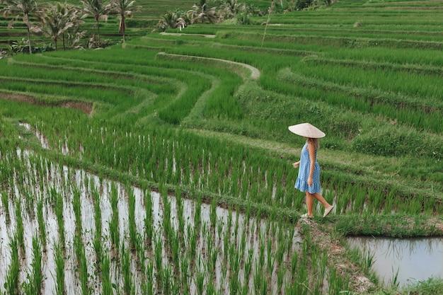 Kobieta spaceruje po tarasach ryżowych na bali