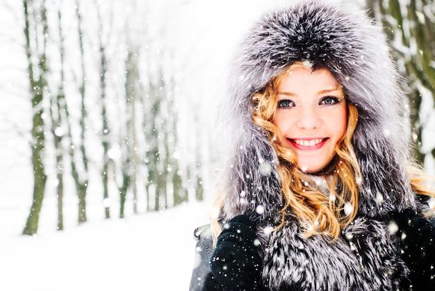 Kobieta spaceruje w alejce w parku zimą