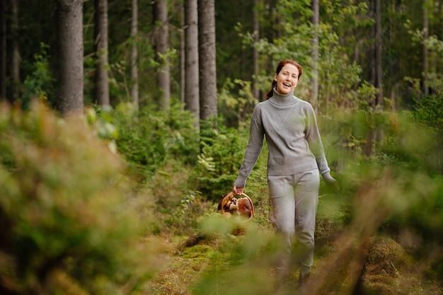 Kobieta spaceruje w letnim lesie zbierając grzyby w koszu koncepcja wędrówki i żywności ekologicznej