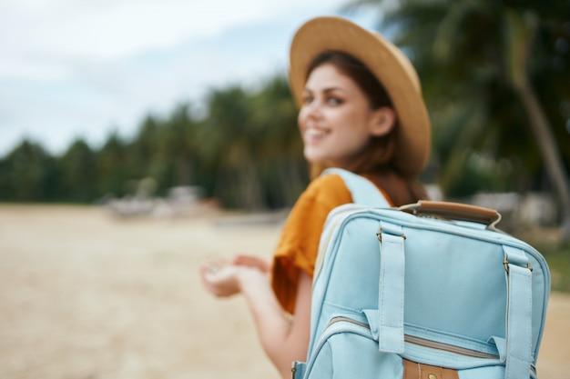Kobieta spaceruje wzdłuż tropikalnej plaży z palmami
