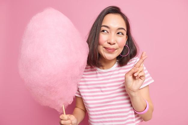 Kobieta spełnia życzenia marzenia się spełniają, trzyma kciuki, nosi luźną koszulkę w paski, która trzyma smaczną watę cukrową