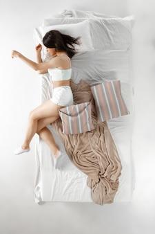 Kobieta śpi i odpoczywa sama w łóżku, marzy. widok z góry z góry
