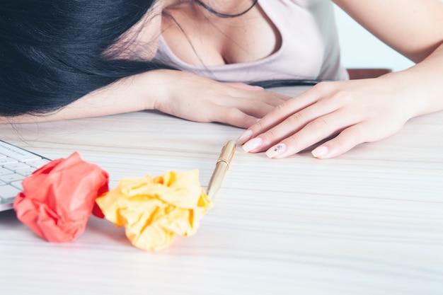 Kobieta śpi na biurku przed zmiętymi kawałkami papieru