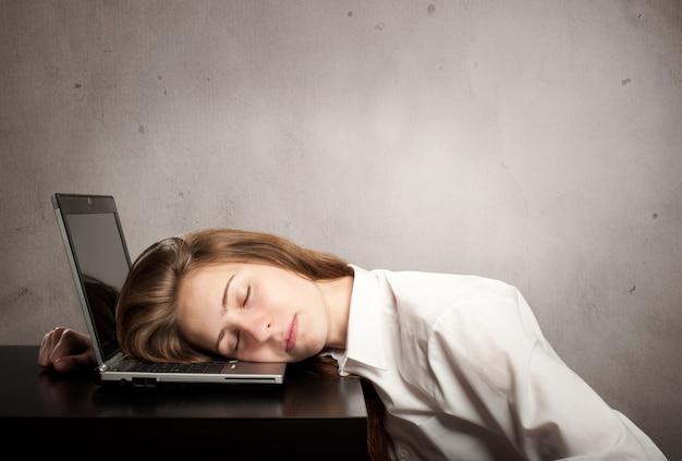 Kobieta śpi na laptopie