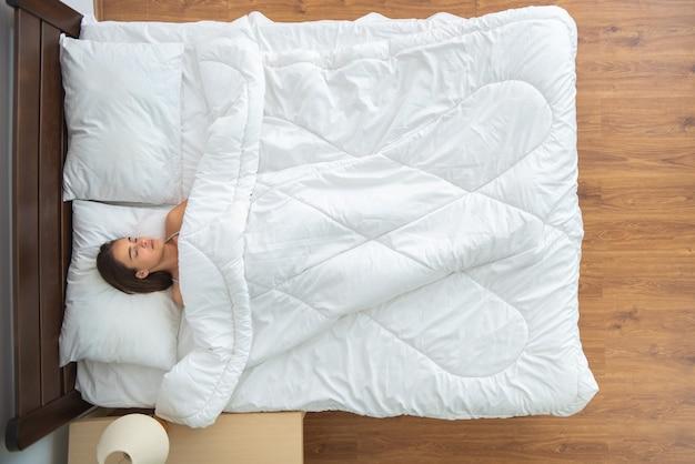 Kobieta śpi na łóżku. widok z góry