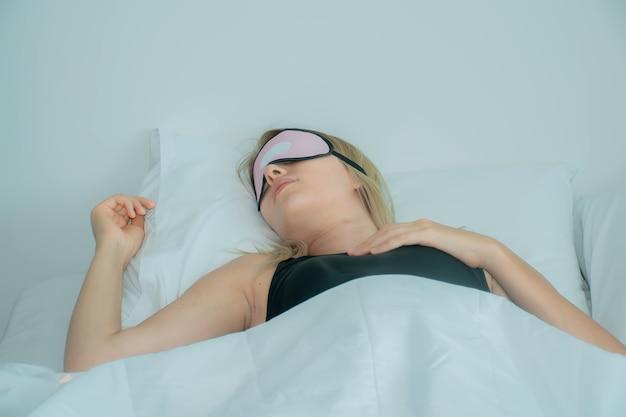 Kobieta śpi na łóżku z maską do spania