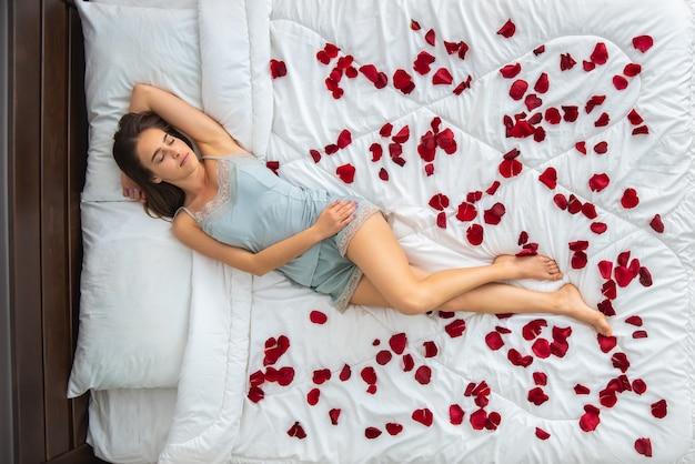 Kobieta śpi na łóżku z płatkami róż. widok z góry
