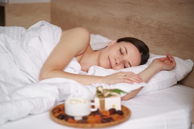 Kobieta śpi na łóżku z prezentem i kawą z piankami stojącymi obok niej.