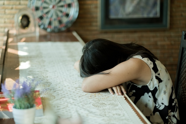 Kobieta śpi na stole, czuje się chory, dama chora, ból dziewczyny