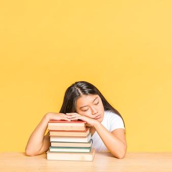 Kobieta śpi na stosie książek