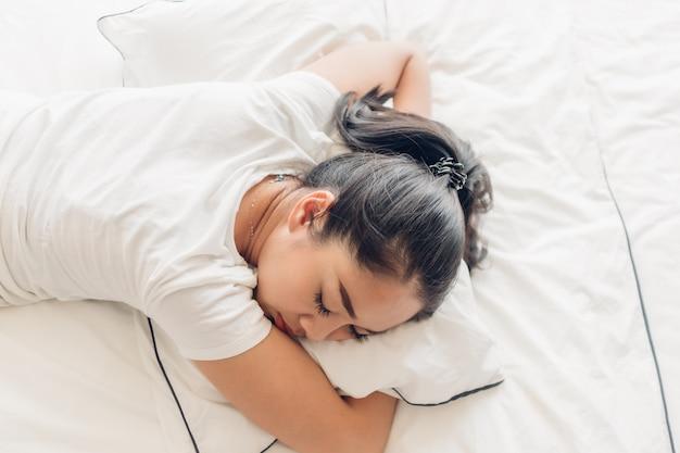 Kobieta śpi na swoim białym łóżku w mieszkaniu.