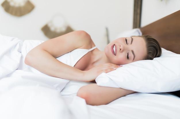 Kobieta śpi. piękna młoda uśmiechnięta kobieta śpi w łóżku