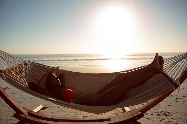 Kobieta śpi w hamaku na plaży