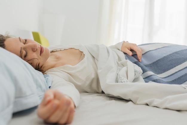 Kobieta śpi w swoim łóżku