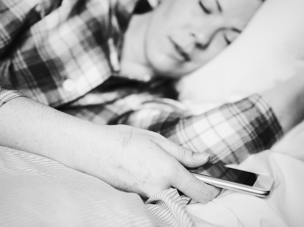 Kobieta śpi z telefonem komórkowym w ręku
