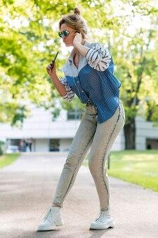 Kobieta śpiewa i tańczy w parku
