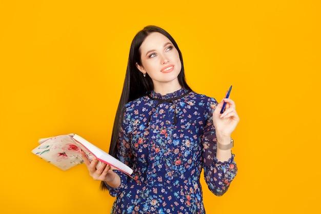 Kobieta spisuje swoje pomysły, trzymając długopis w ręce podniesionej do góry, a notatnik w drugiej ręce na żółtej ścianie. planowanie koncepcji, kobieta biznesu, pomysł na biznes.