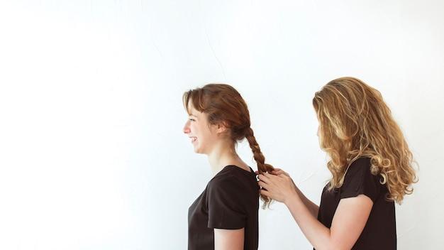 Kobieta splata siostry włosy odizolowywającego nad białym tłem