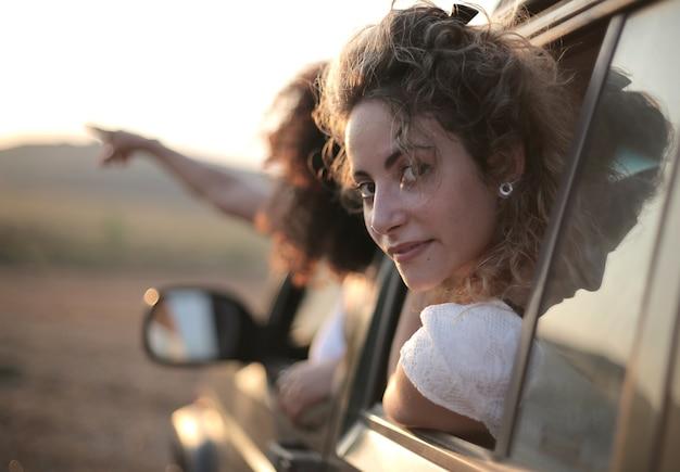 Kobieta spoglądająca przez okno samochodu za drugą, wskazującą palcem