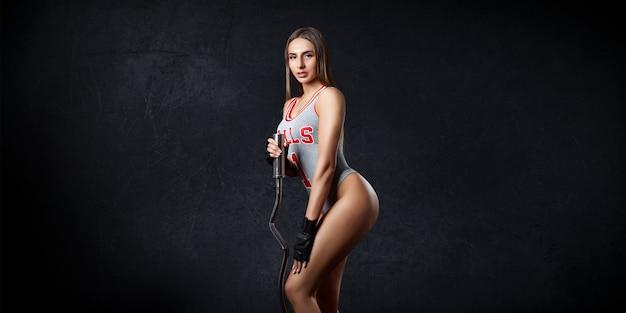 Kobieta sport fitness pociągi na ciemnej ścianie. portret dziewczynki uprawiającej sport, piękne ciało, pozbywanie się nadwagi, trener fitness.