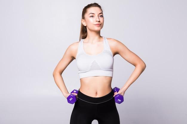 Kobieta sport fitness z hantlami na białym tle na białej ścianie