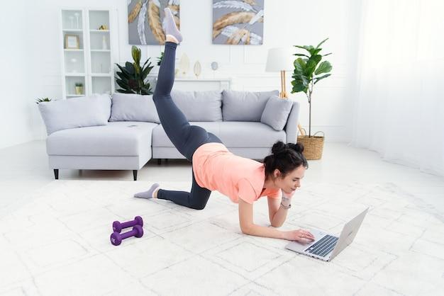 Kobieta sport robi ćwiczenia na podłodze w domu i ogląda filmy fitness na laptopie.