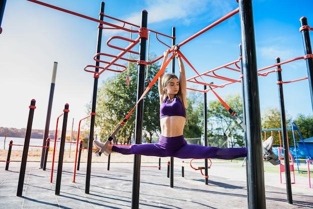 Kobieta sport robi trening na świeżym powietrzu z trx w ciągu dnia