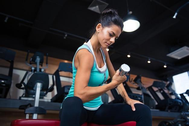 Kobieta sport trening z hantlami na ławce w siłowni