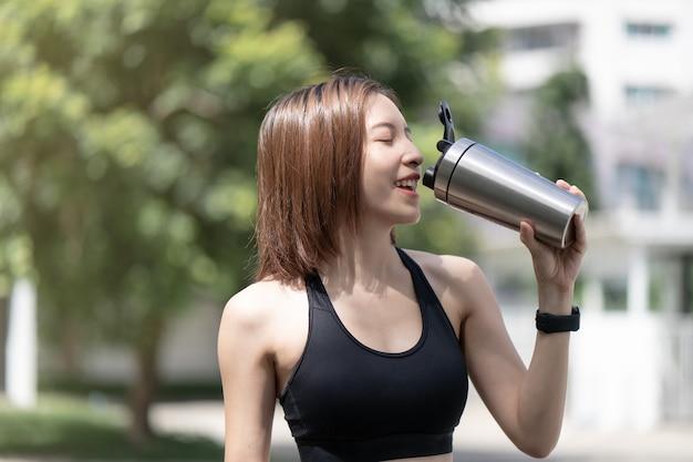 Kobieta sportowa pije shake proteinowy z wytrząsarki do butelek blendera ze stali nierdzewnej na naturalnym zielonym tle.