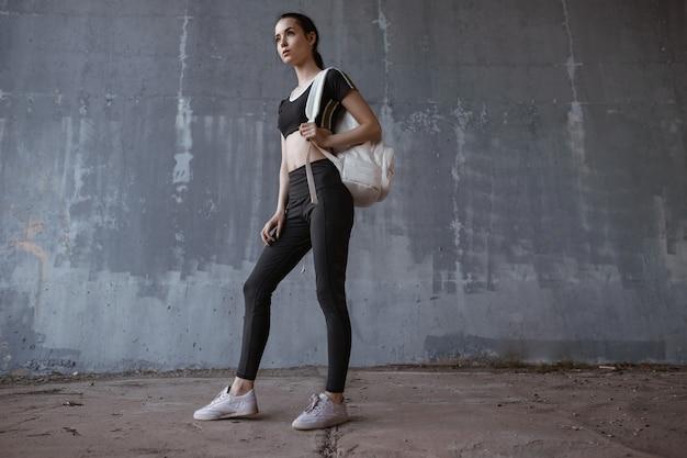 Kobieta sportowa pozowanie w odzieży sportowej moda na miejskiej szarej ścianie.