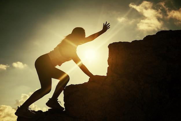 Kobieta sportowca wędrującego prosi o pomoc na szczycie