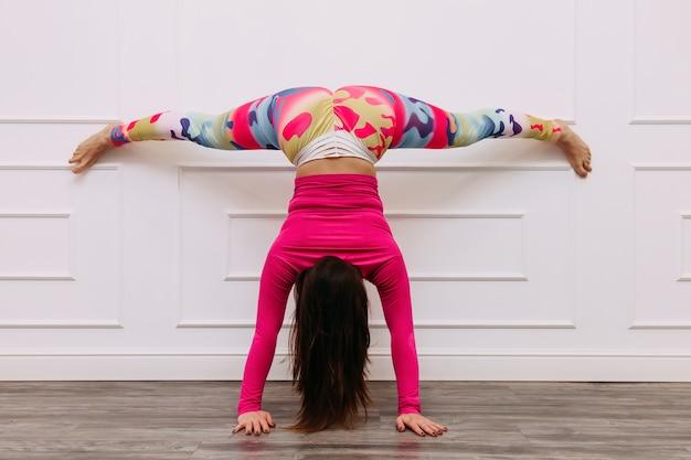Kobieta sportowiec fitness szkolenia ramiona i nogi głową w dół o ścianę