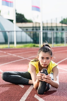 Kobieta sportowiec rozciągający się na torze wyścigowym przed uruchomieniem