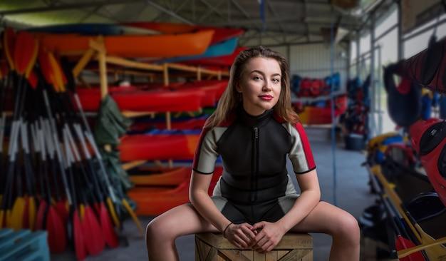 Kobieta sportowiec w kombinezonie, łodziach i sprzęcie do nurkowania. wypożyczalnia łodzi lub stacja ratownicza