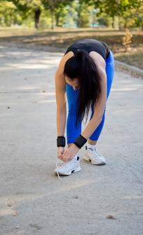 Kobieta-sportowiec w stroju sportowym pochyla się i zawiązuje sznurowadła na swoich butach przed rozpoczęciem ćwiczeń w parku
