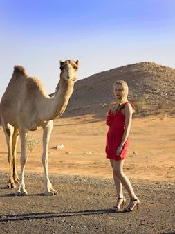 Kobieta spotyka dzikiego wielbłąda na pustyni poza drogą