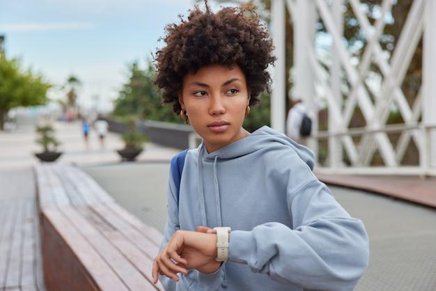 Kobieta sprawdza czas na zegarku czeka, aż trener rozpocznie trening, nosi luźną bluzę z kapturem pozuje na zewnątrz