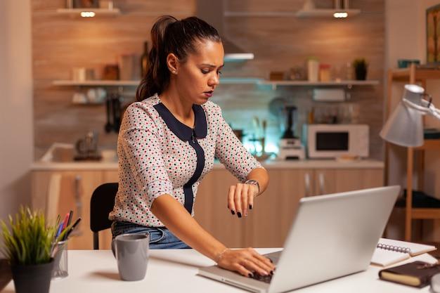Kobieta sprawdza czas na zegarku podczas pracy w domu