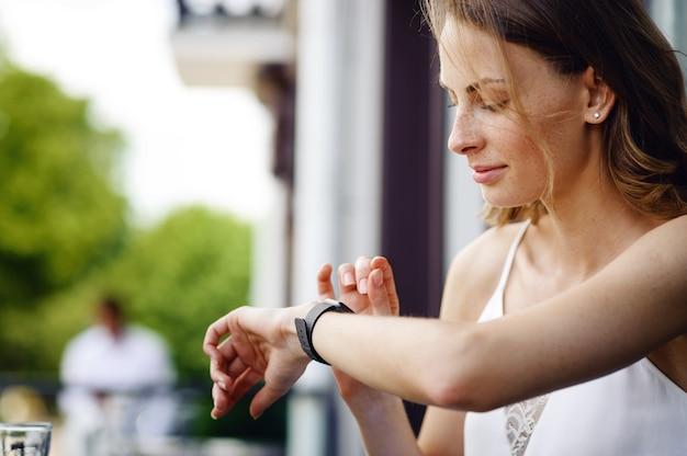 Kobieta sprawdza godzinę na swoich inteligentnych zegarkach