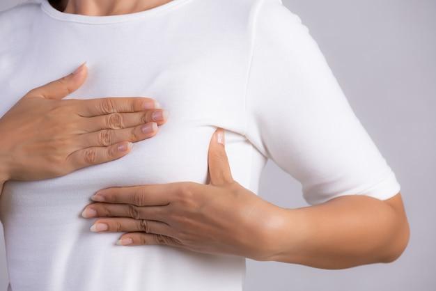 Kobieta sprawdza guzki na piersi pod kątem oznak raka piersi