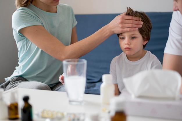 Kobieta sprawdza jego syna dla gorączki