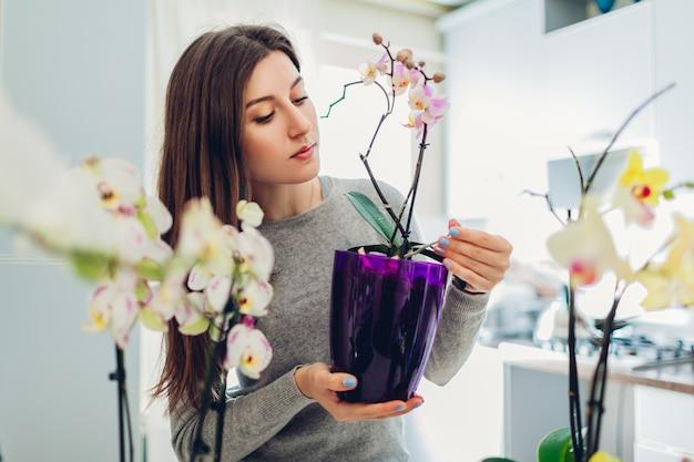 Kobieta sprawdza jej orchidee w kuchni. szczęśliwa gospodyni domowa dbająca o rośliny domowe i kwiaty.