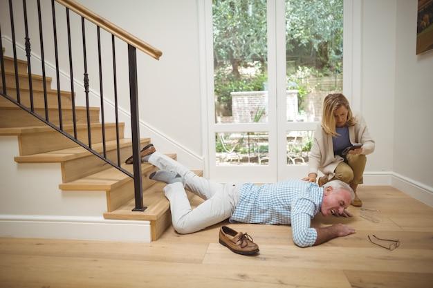 Kobieta sprawdza jej telefon komórkowy, podczas gdy starszy mężczyzna upadł na dole