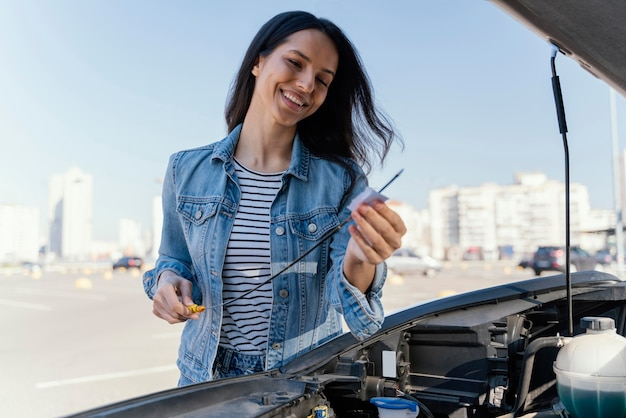 Kobieta sprawdza olej w swoim samochodzie