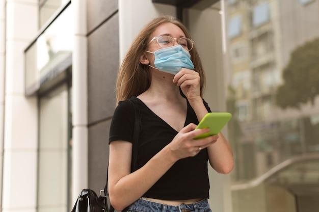 Kobieta sprawdza swój telefon w masce medycznej na zewnątrz