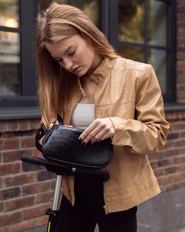 Kobieta sprawdza swoją torbę podczas jazdy na hulajnodze elektrycznej na świeżym powietrzu