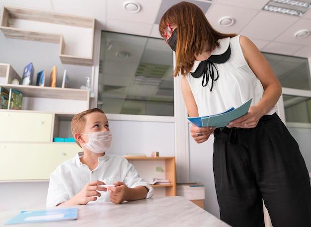 Kobieta sprawdza swojego ucznia w klasie podczas pandemii