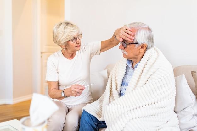 Kobieta sprawdza temperaturę gorączki starszego mężczyzny