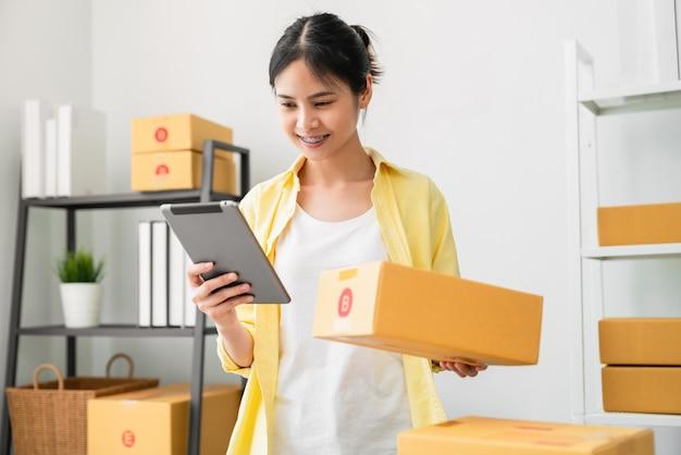 Kobieta sprawdza zamówienie online na cyfrowy tablet i pudełka do pakowania